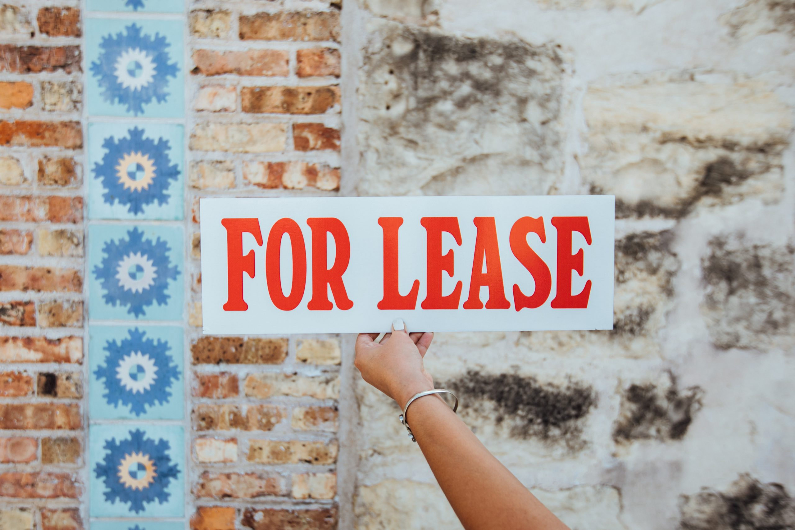 a hand holding a for lease sign